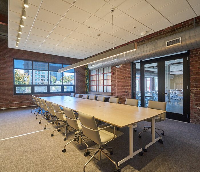 Sara and Bill Morgan Board Room with brick wall and conference room table and windows.