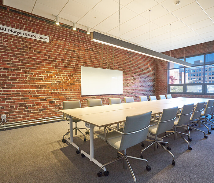 Sara and Bill Morgan Board Room with brick wall and conference room table with light above.