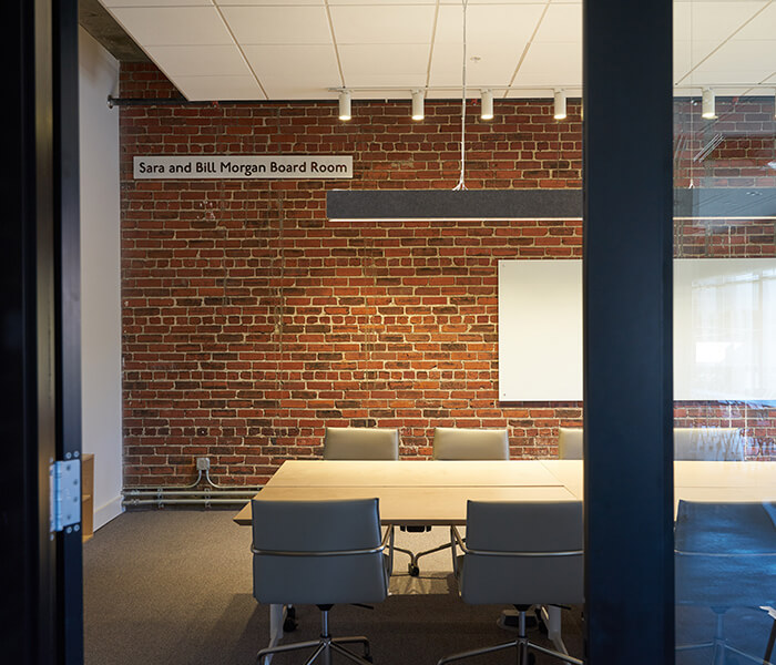 Looking into the Sara and Bill Morgan Board Room with brick wall, conference room table, and live above.