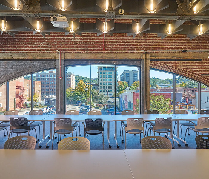 The Michael Sherrill Loft with tables set up and large windows overlooking downtown Asheville.