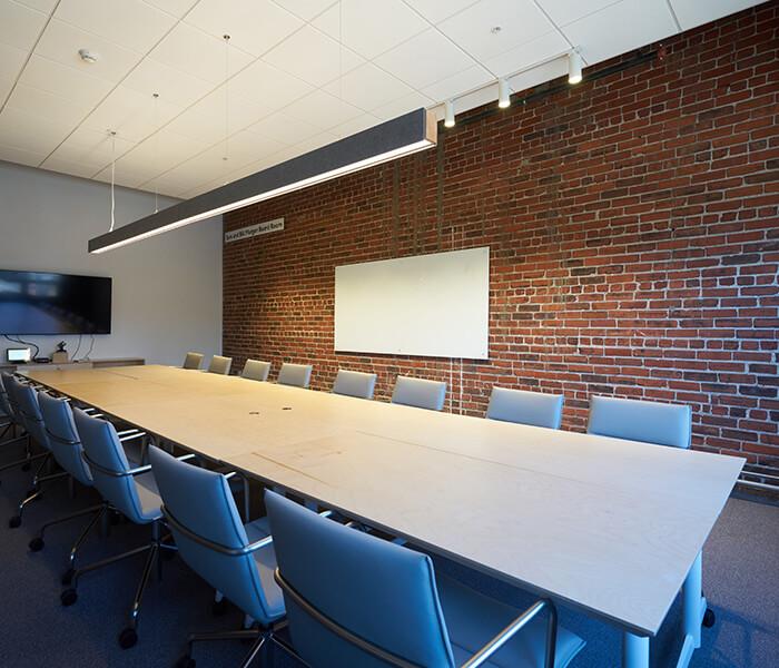 Sara and Bill Morgan Board Room with brick wall and conference room table.