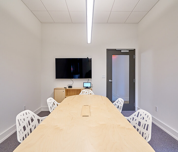 Conference room with long wooden table and chairs around it with a screen on the wall.