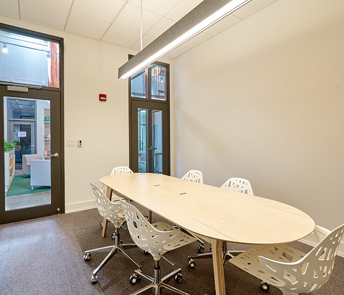 Conference room with large wooden table and six chairs.