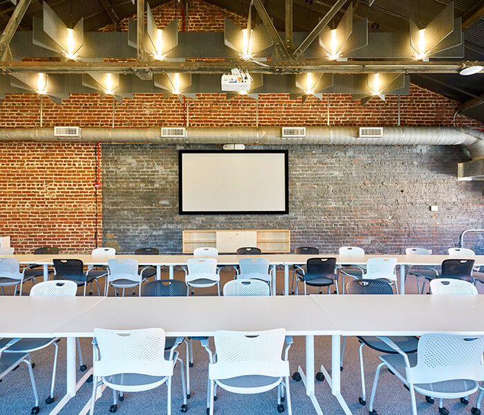 Classroom set up with screen on exposed brick wall.