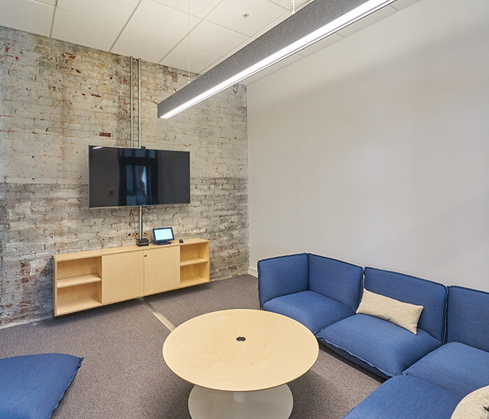Small conference room with soft seating and television screen.