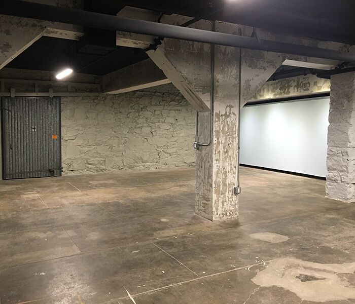 Industrial space with concrete pillars and projector screen.