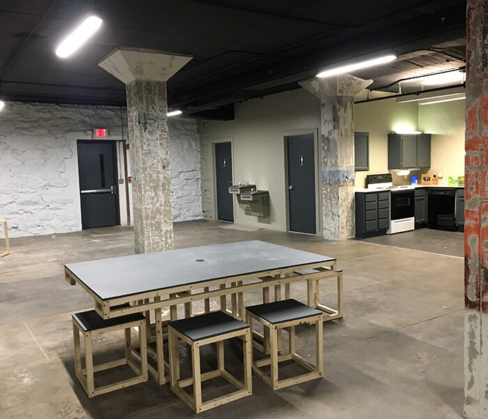 Industrial space with small table and kitchenette.