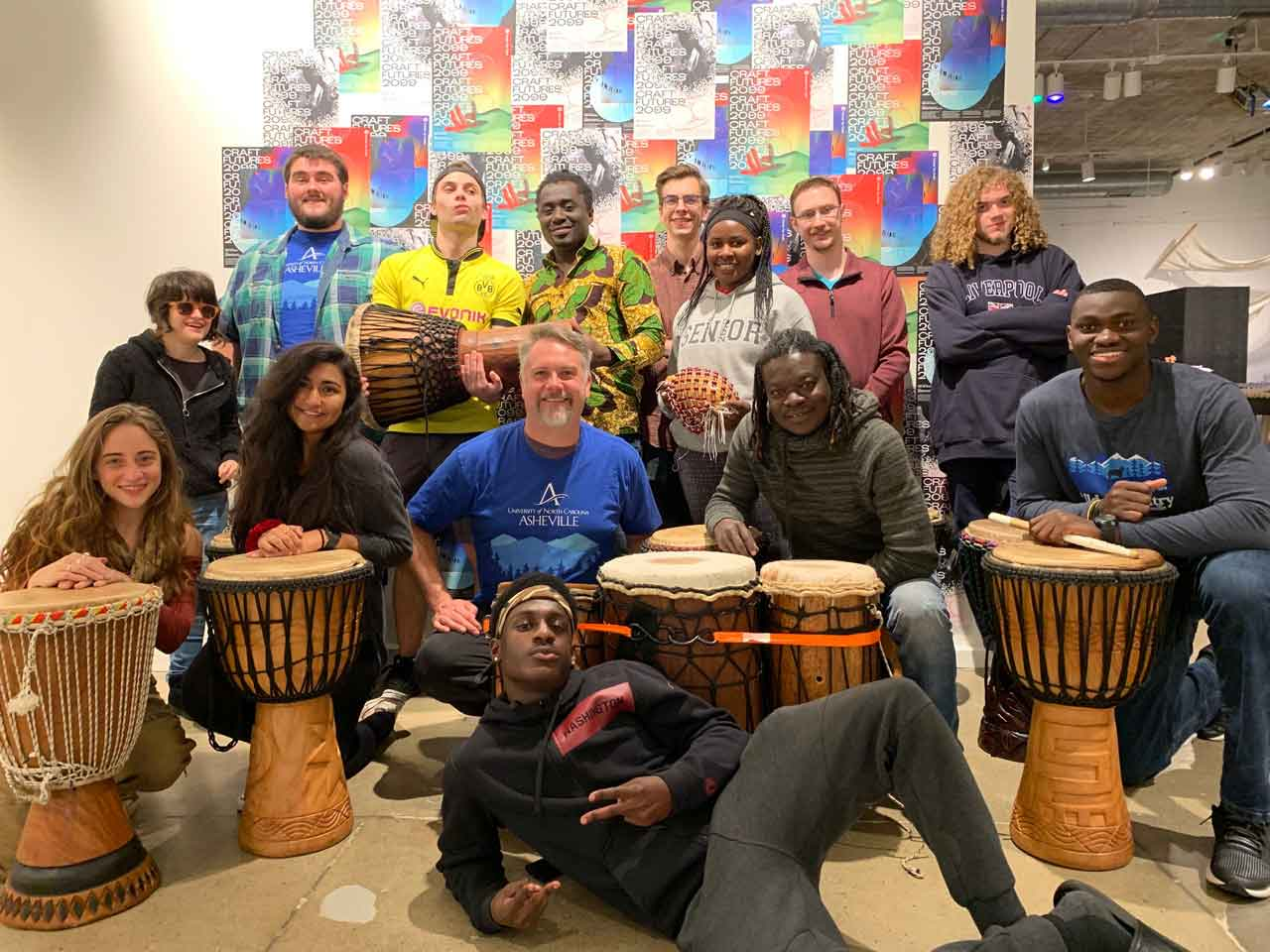 Fourteen people gathered together and smiling and posing with African drums.
