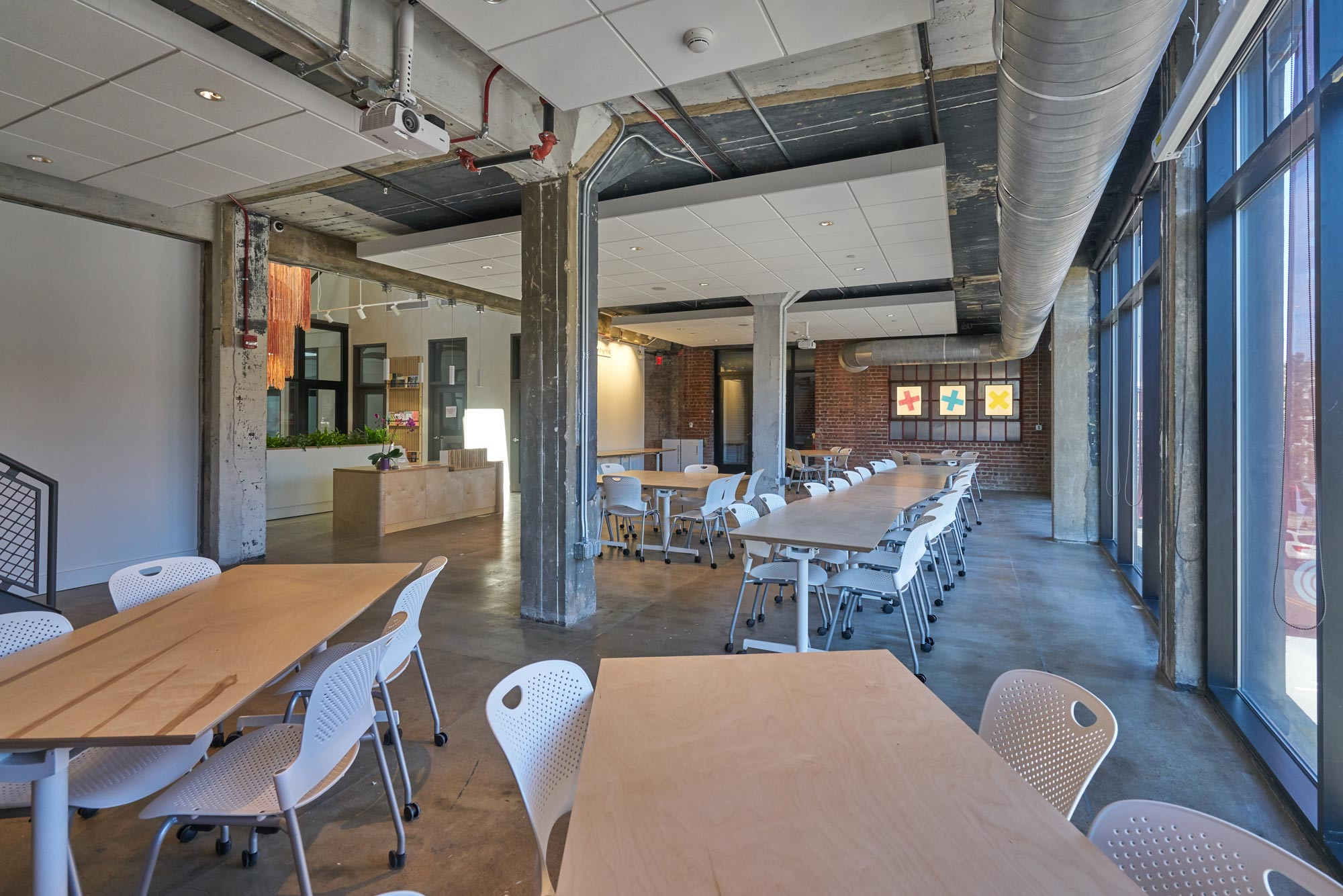 An industrial, open spaces with exposed brick and many tables and chairs.