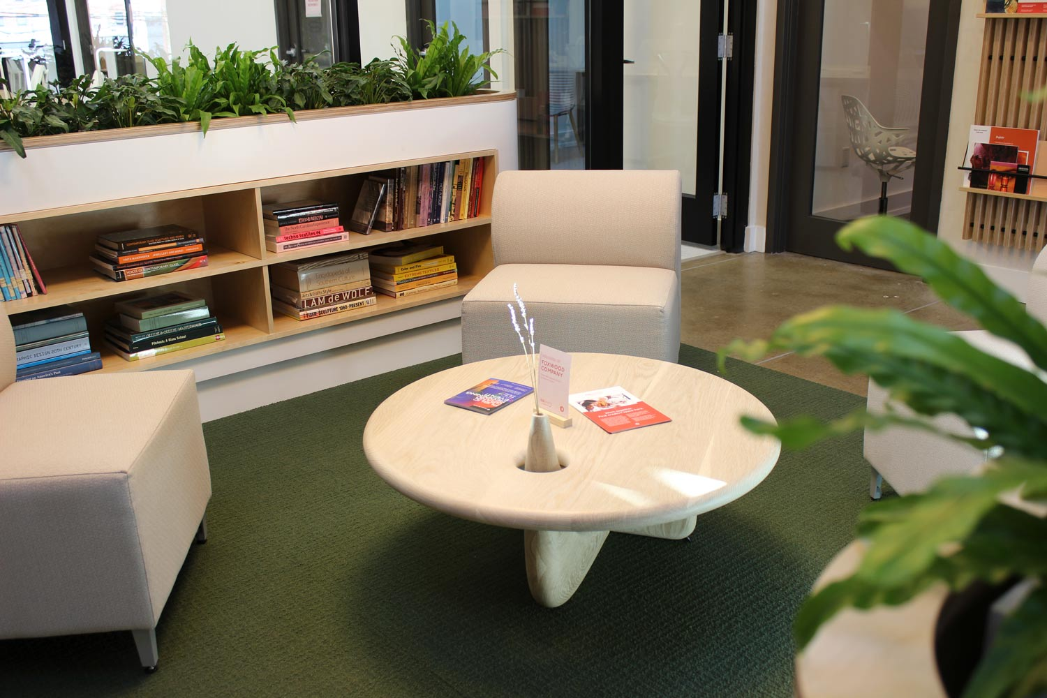 A seating area with two plush chairs, a small table, and a bookshelf.