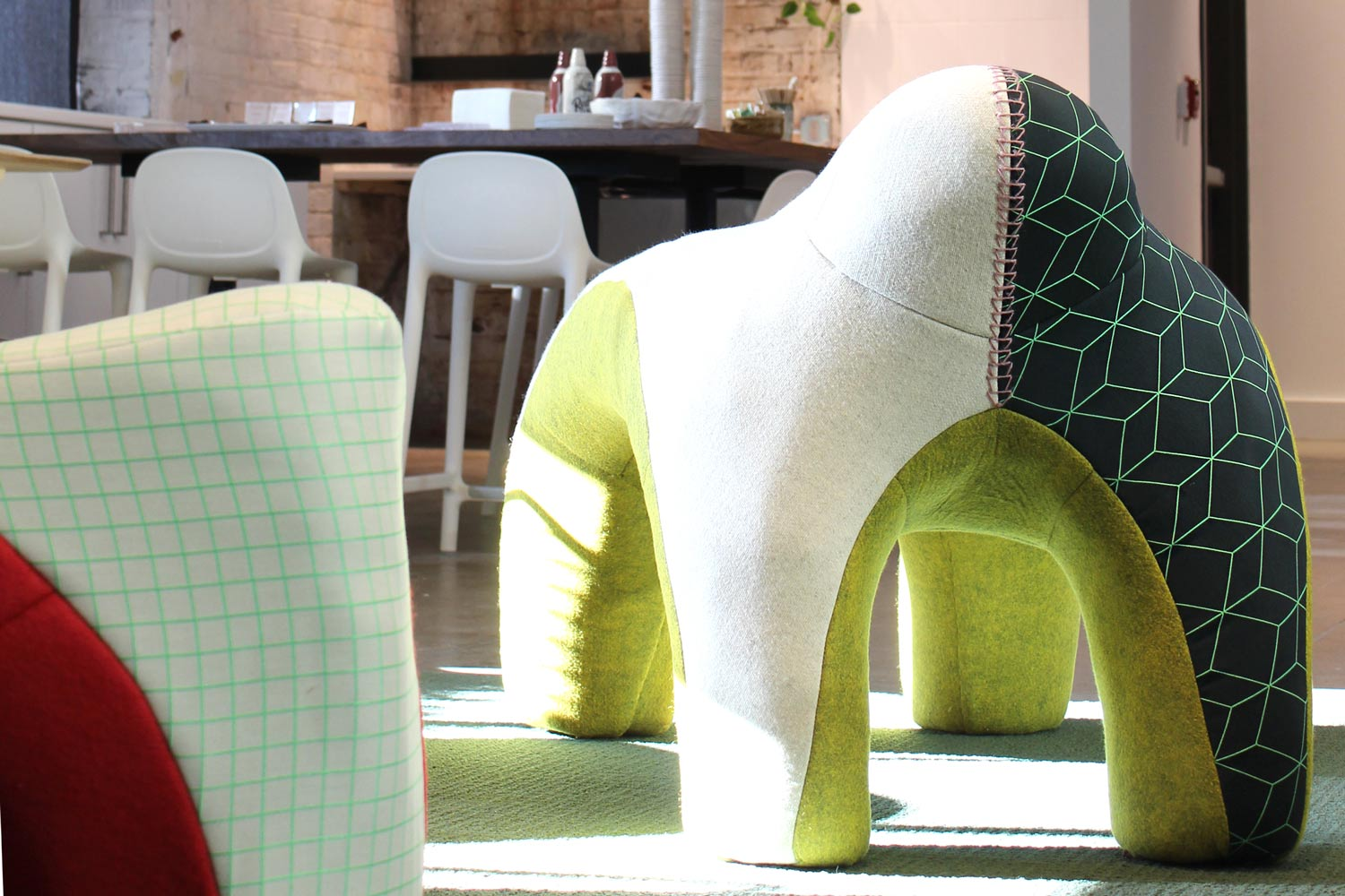 A green and white plush piece of furniture with four legs.