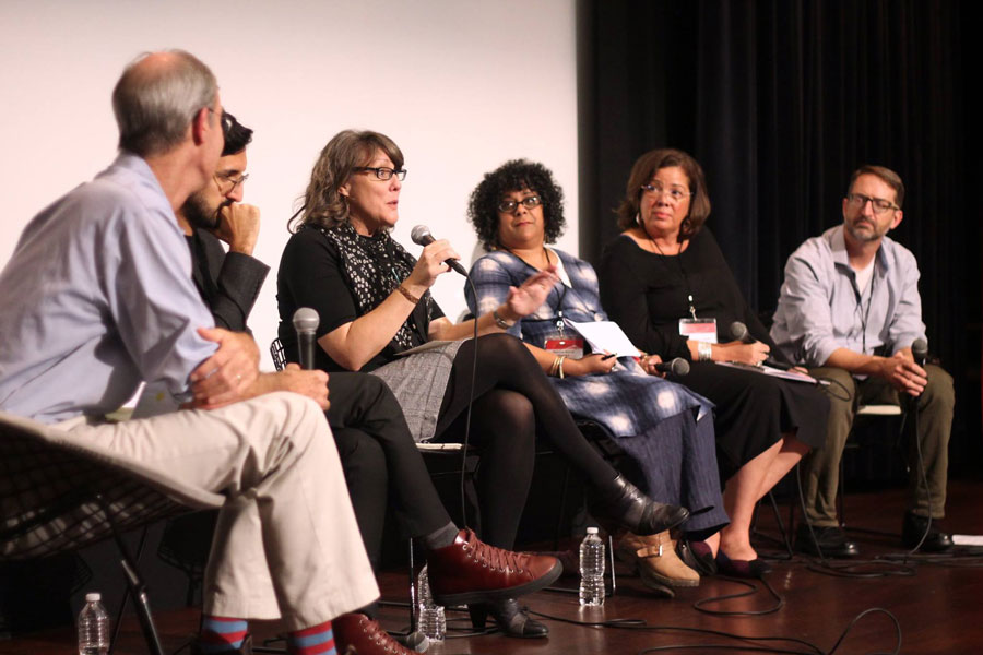 Panel of six people on a stage with one woman holding a microphone and speaking.