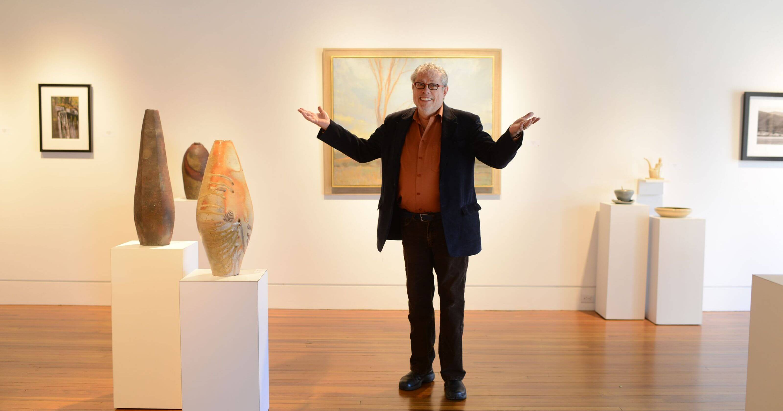 John Cram in a gallery with his hands lifted up to showcase it.