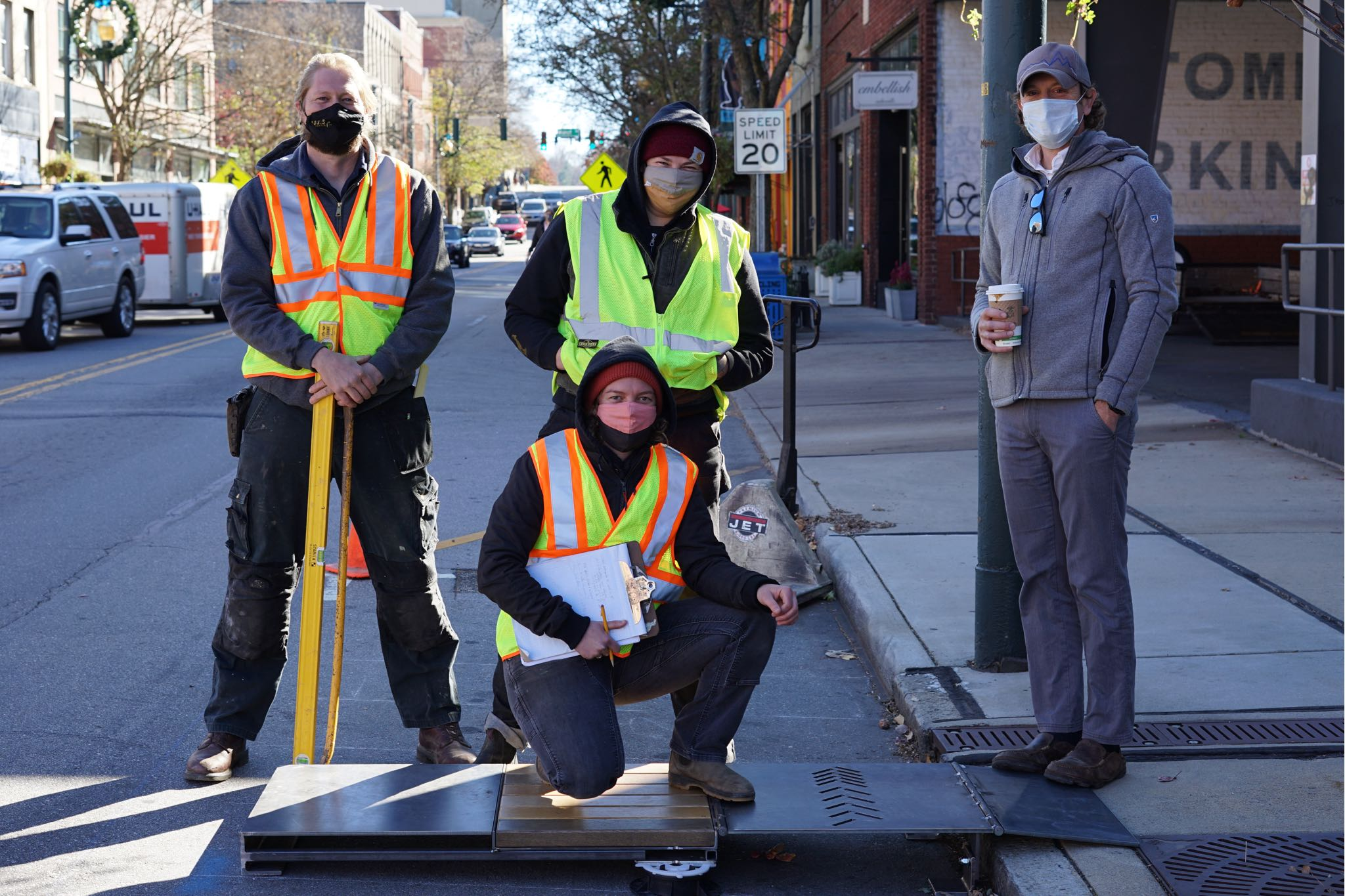 Four people posing with metal and wooden prototype for the Cherokee Parklet.