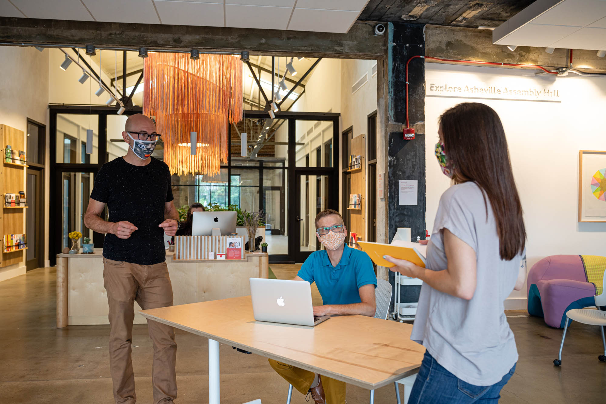 Coworking space with three people gathered with masks on