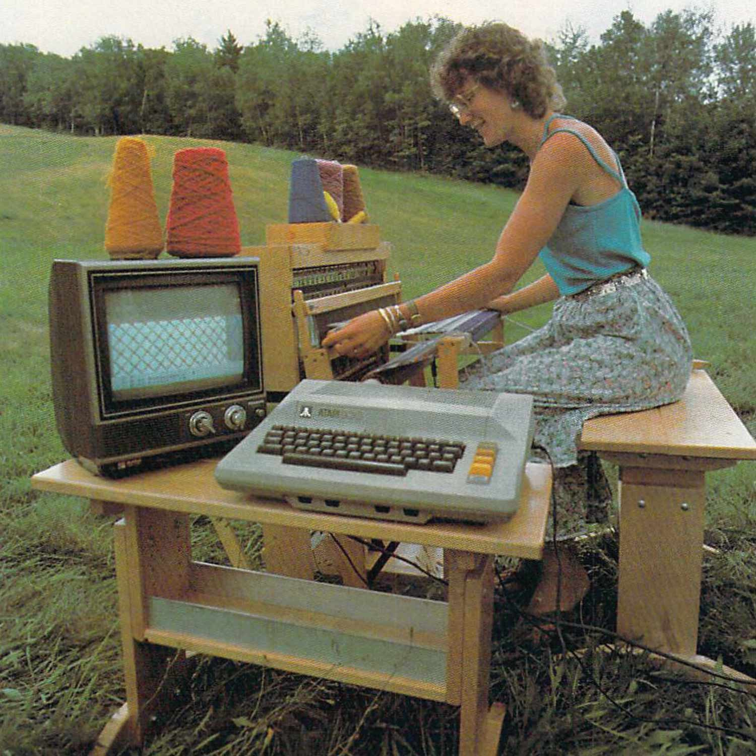 Retro image of Janice Laurie in a field with a tv monitor and typewriter connected to a weaving loom.