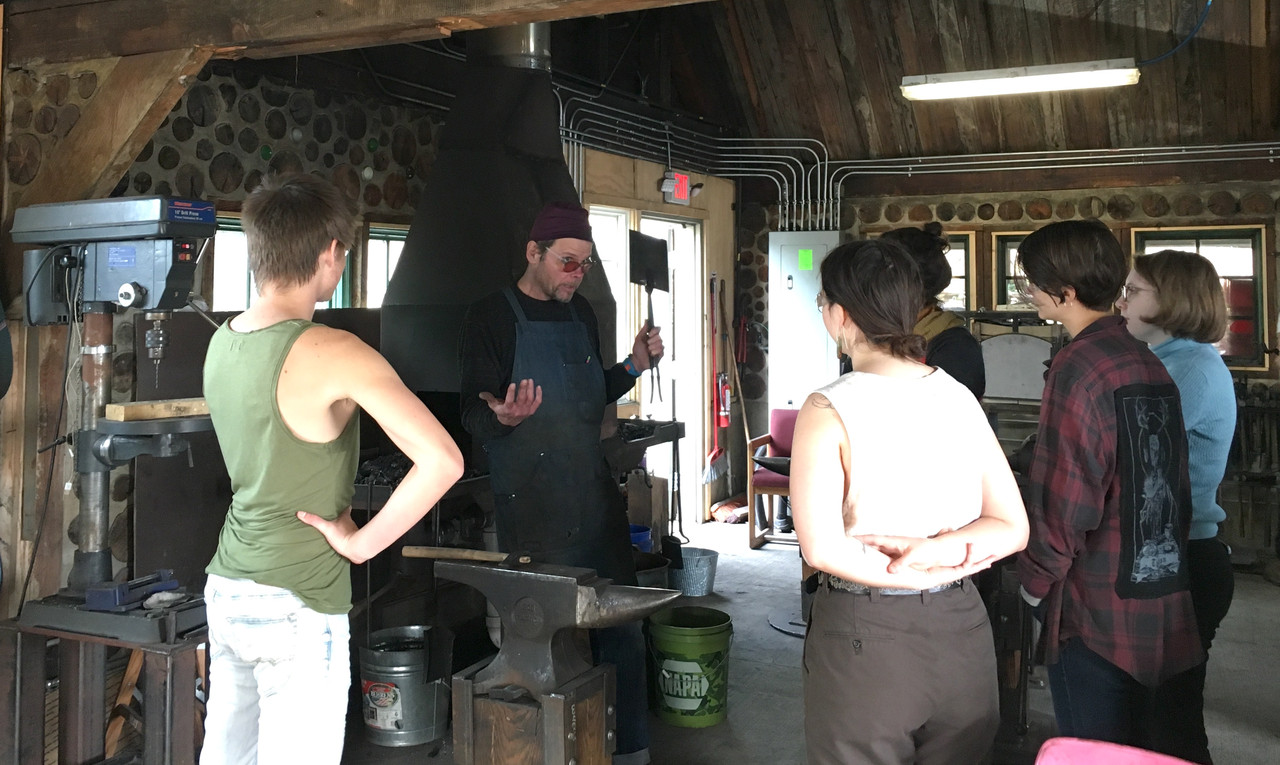 Students learning blacksmithing from an instructor standing next to a forge.