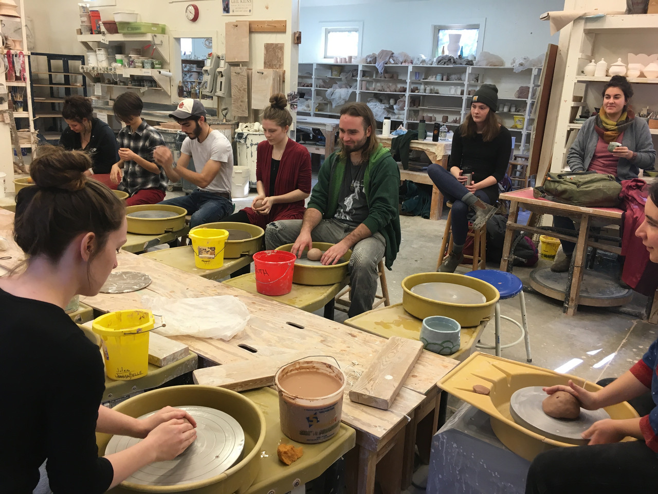 Students sitting at wheels spinning pots in a ceramic class.