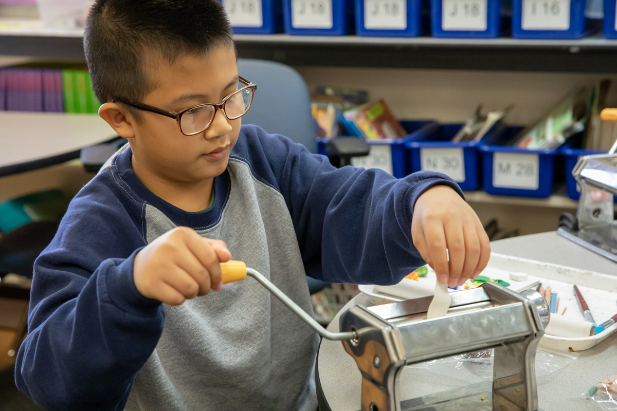 A student at Ibarra Elementary uses a hand-cranked machine to prepare clay for a project.