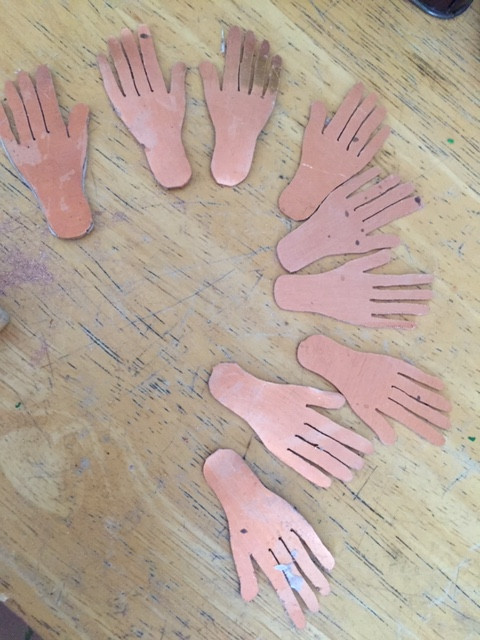 A close-up in-process shot of some copper hands arranged on a table.