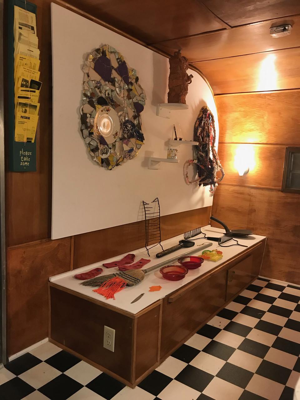 An exhibit of mended things in a camper van gallery space.