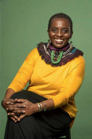 Professional headshot of smiling older black woman wearing ornate jewelry, posing on a stool.