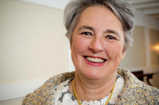 Smiling white woman professional headshot with short grey hair.