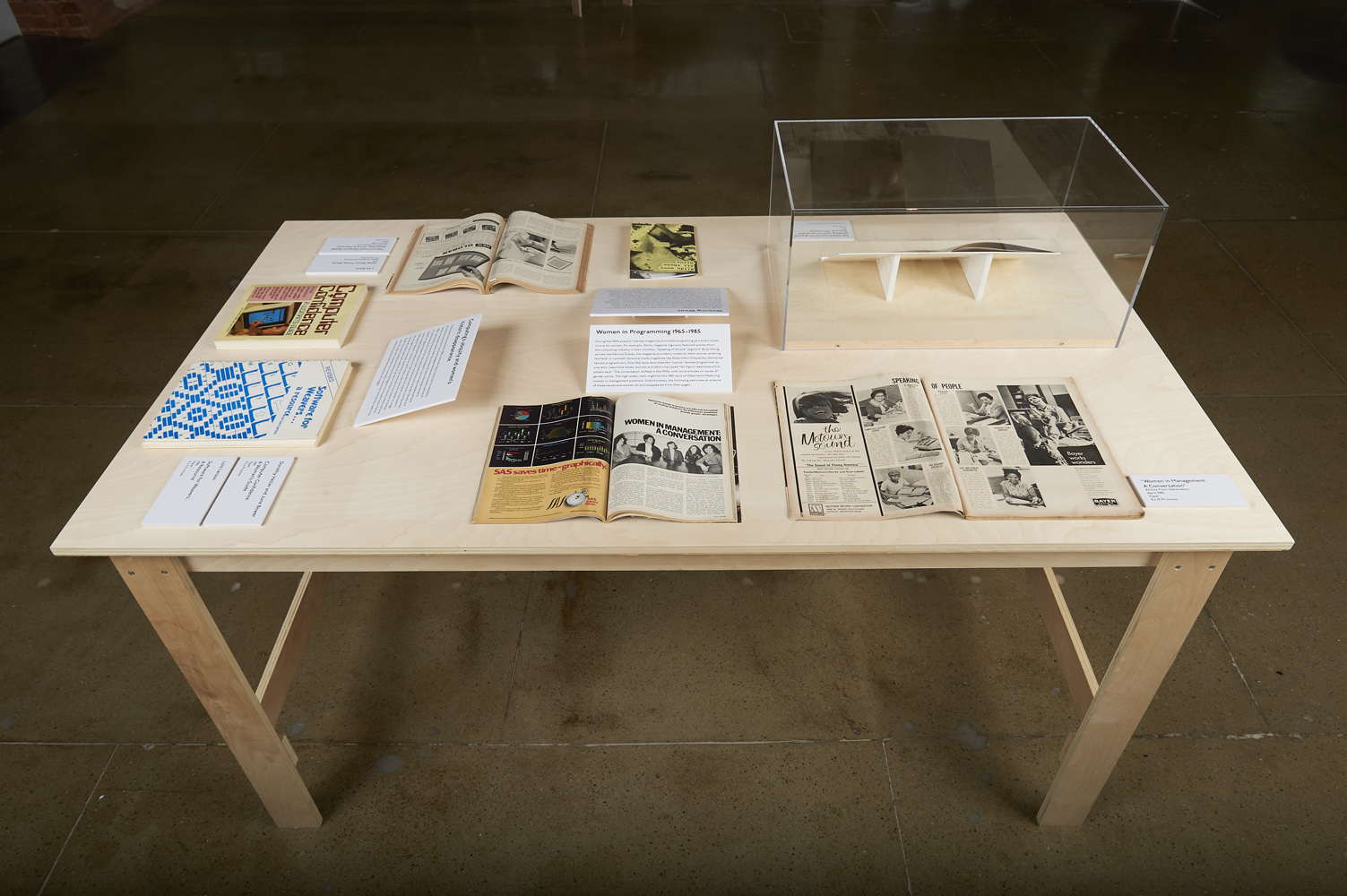 "table at gallery exhibition title ""The Computer Pays Its Debt"" showcasing several old book and magazine publications"