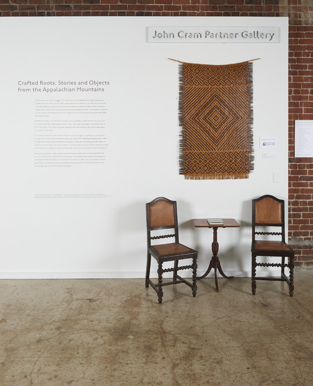 "Image of introductory text and woven basket wall hanging for ""Crafted Roots"" exhibition."