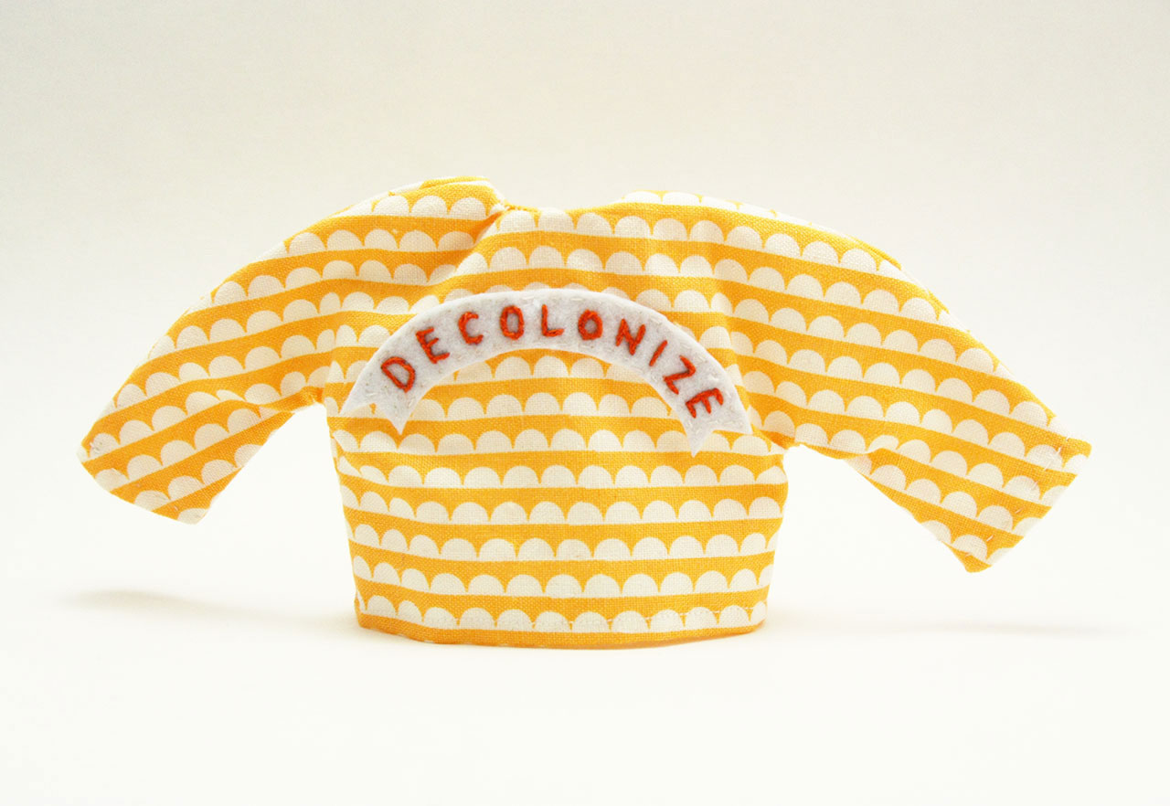 """Tiny yellow and white sweater with word """"Decolonize"""" embroidered on it."""
