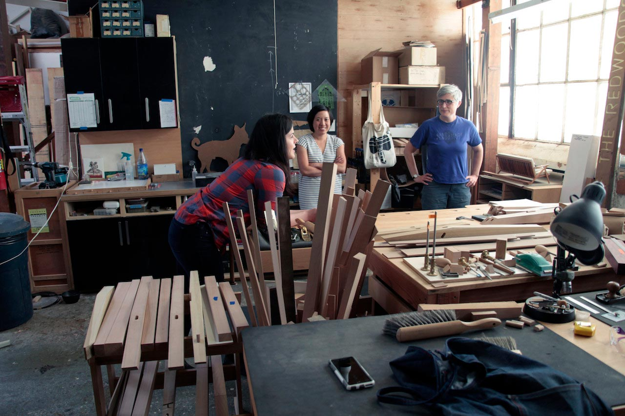 Three people in a woodworking shop having a discussion.
