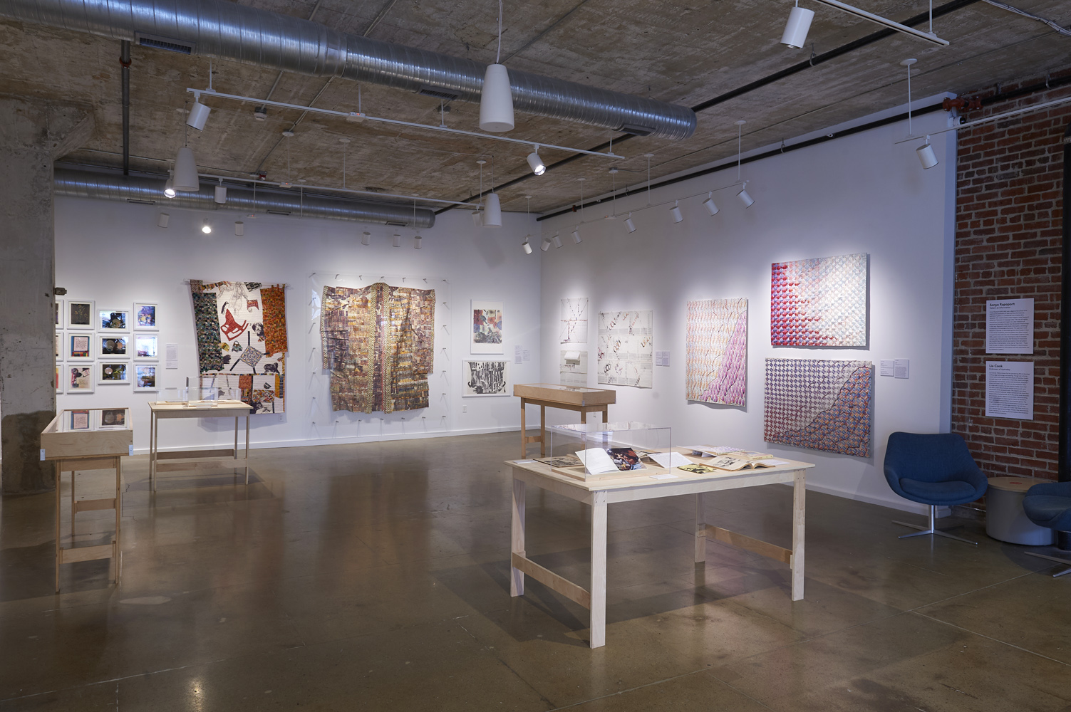 """gallery exhibition for """"The Computer Pays Its Debt"""" in the Center for Craft Bresler Family Gallery, showing an assortment of textiles, clothing, quilts, and publications"""