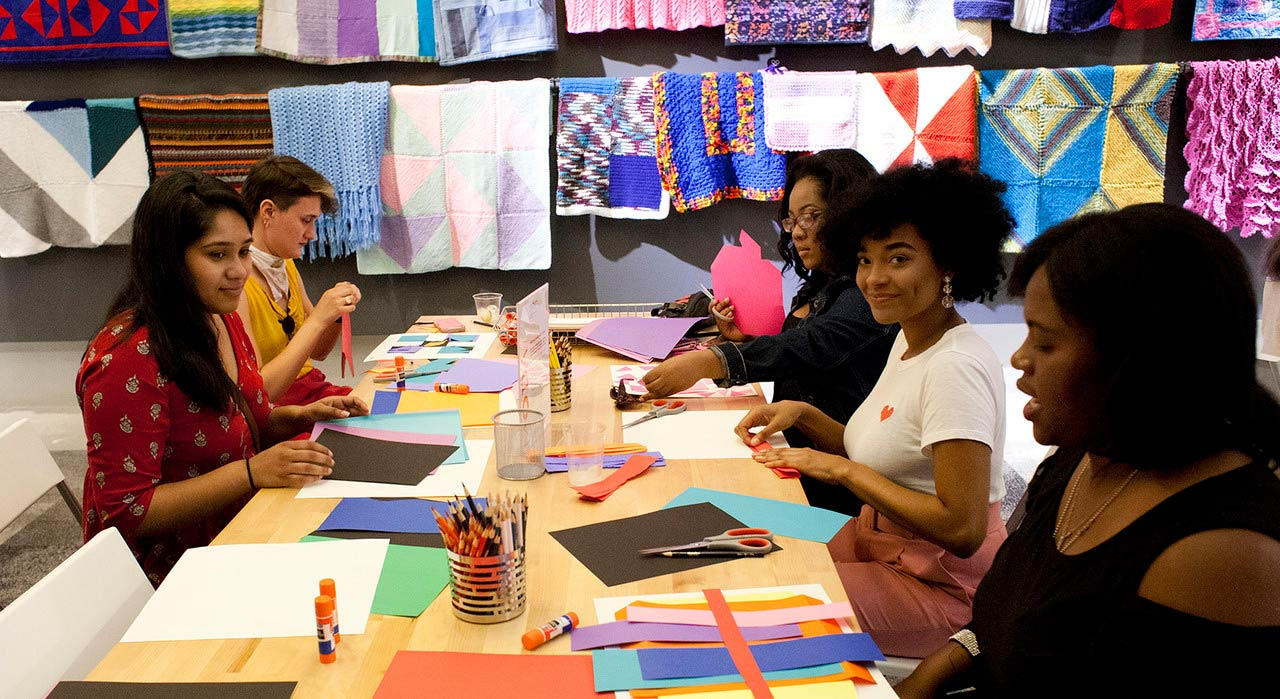 Five people participating in craft activity around a table.