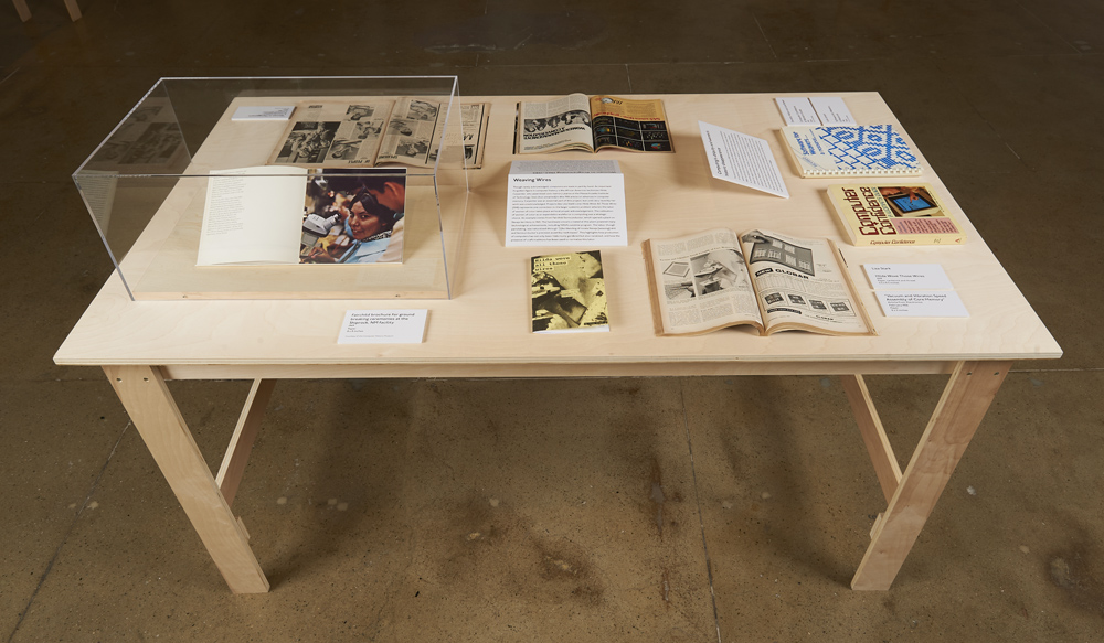 """Birchwood table in Bresler Family Gallery displaying an array of publications and artifacts for """"The Computer Pays Its Debt"""""""