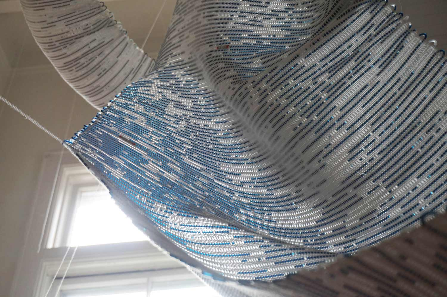 a hanging blue textile in front a window. the window lights up the textile, showing that the textile is woven with tubes filled with blue and clear liquid.