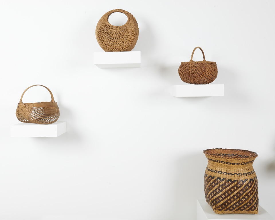 Pictured are four handwoven baskets. Left to right, first three baskets are round with single handles. Last basket has a square bottom and round top, is two-toned, and has an open mouth (no lid or handle).