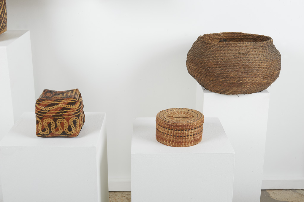 Pictured are three handwoven baskets. Left to right: small, three-toned square basket with lid, small three-toned round basket with round lid, and large, round open mouth basket.