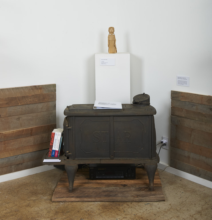 "An old STAR woodstove in ""Crafted Roots"" exhibition, used as bookshelf for exhibition literature. There is a corn husk doll on a white vitrine behind the stove."