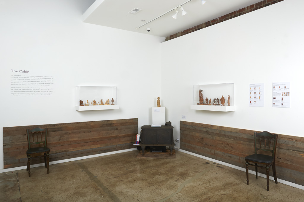 Exhibition photo with wooden figurines and wood stove in view.