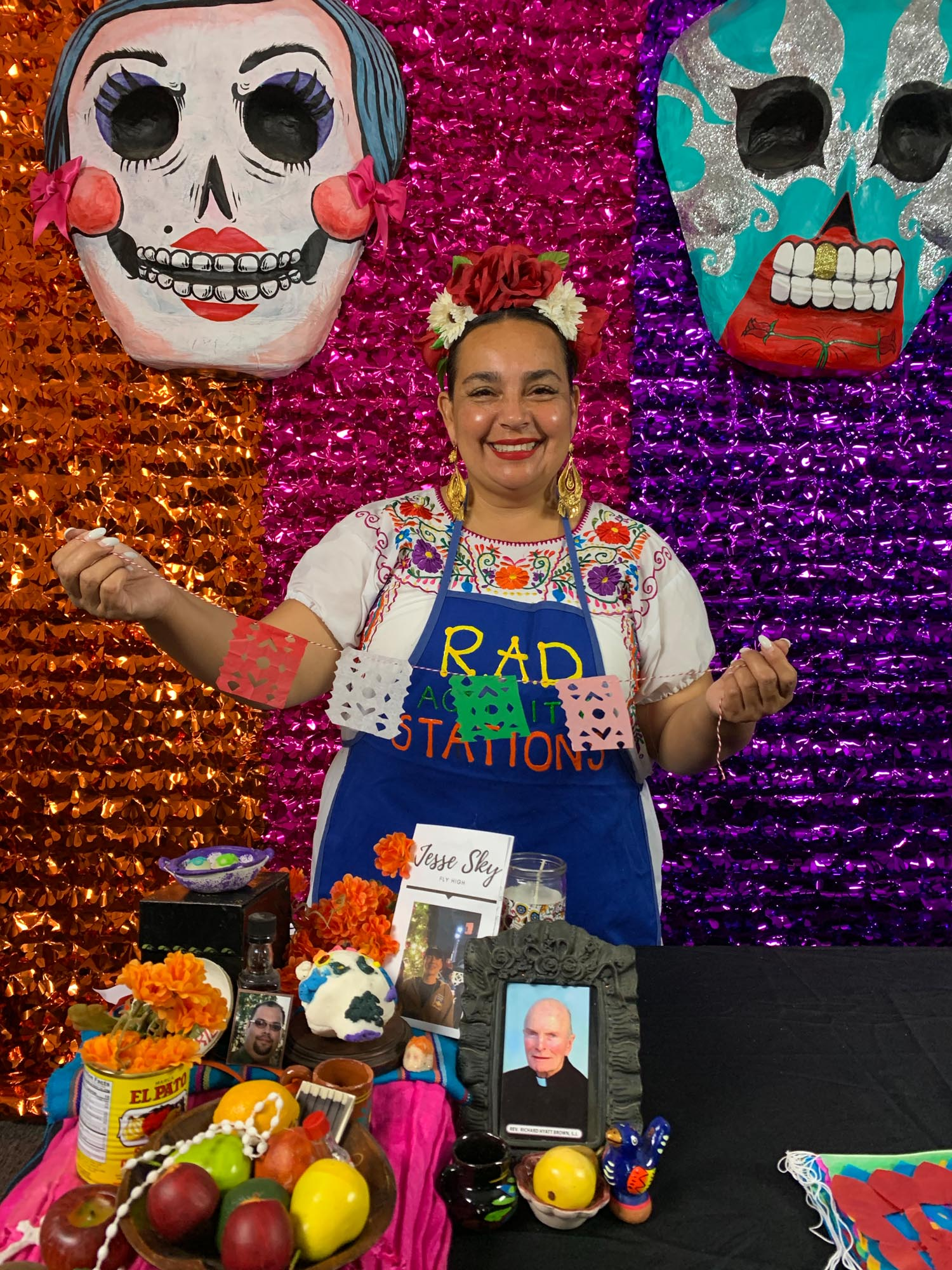woman standing at a dia de los muertos altar, smiling, with traditional mexican clothing and flowers in her hair