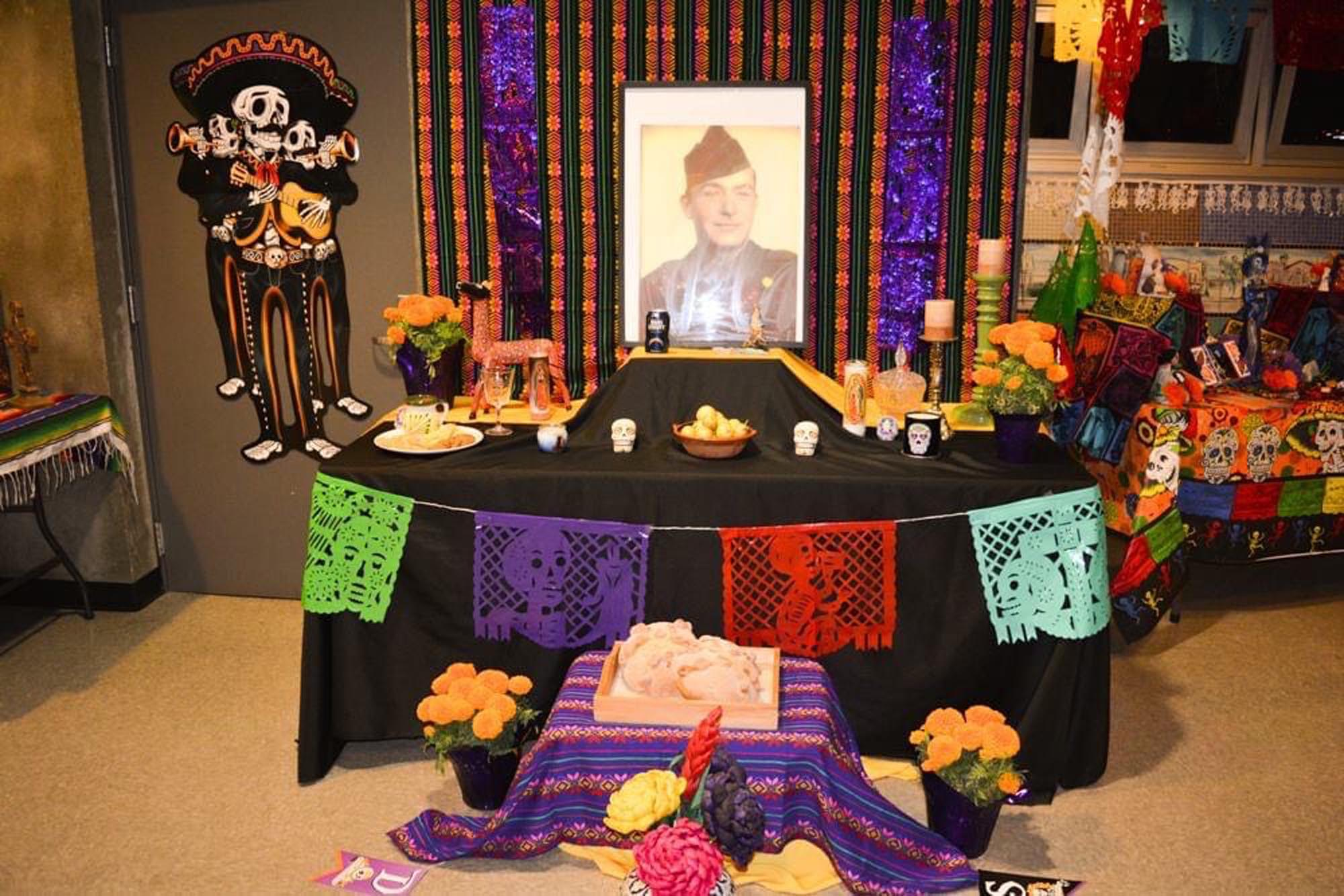 dia de los muertos altar with an old, sepia photo of a man in uniform. the altar has colorful flags and decorations and is indoors