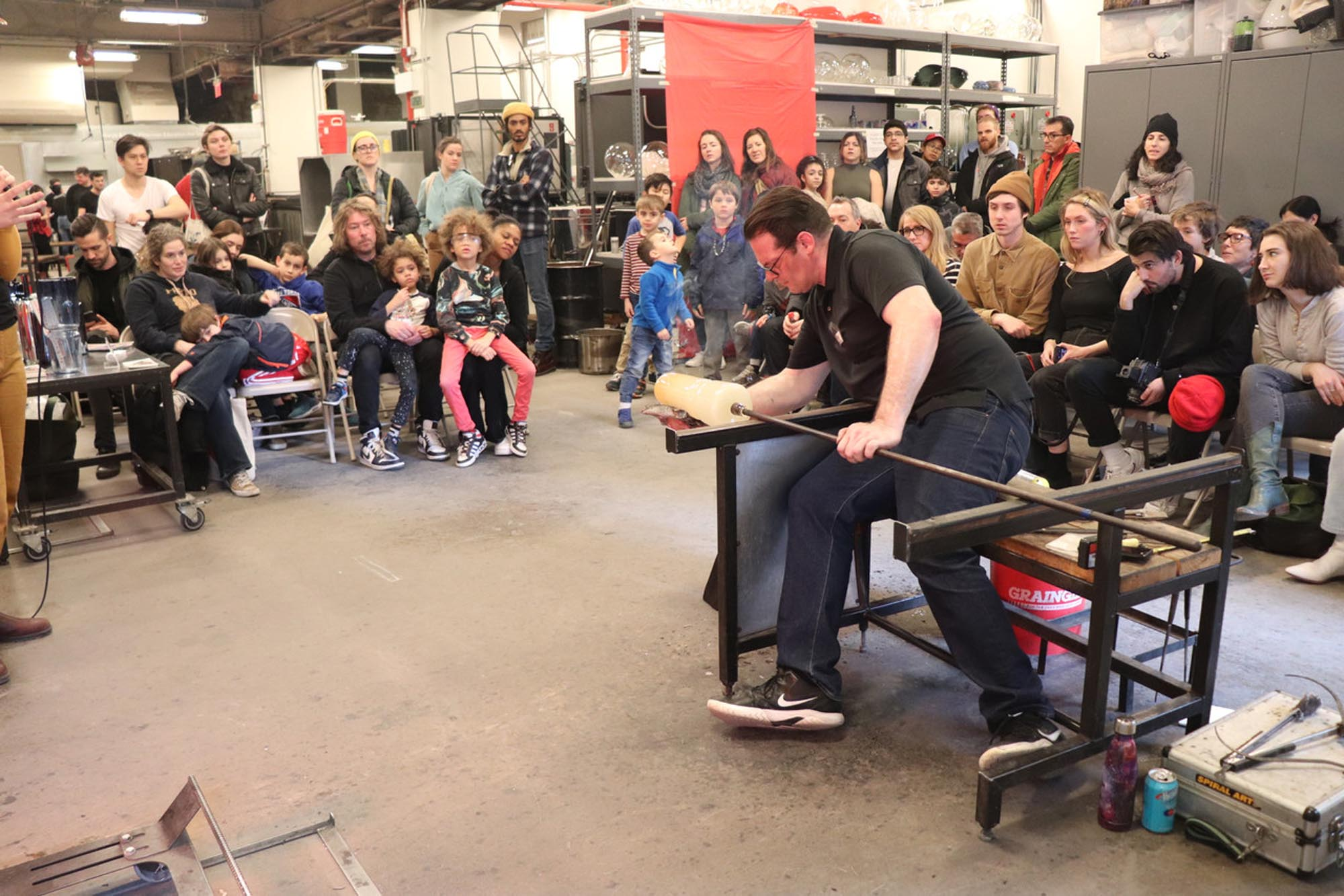 a man doing a glassmaking demonstration in front of an audience