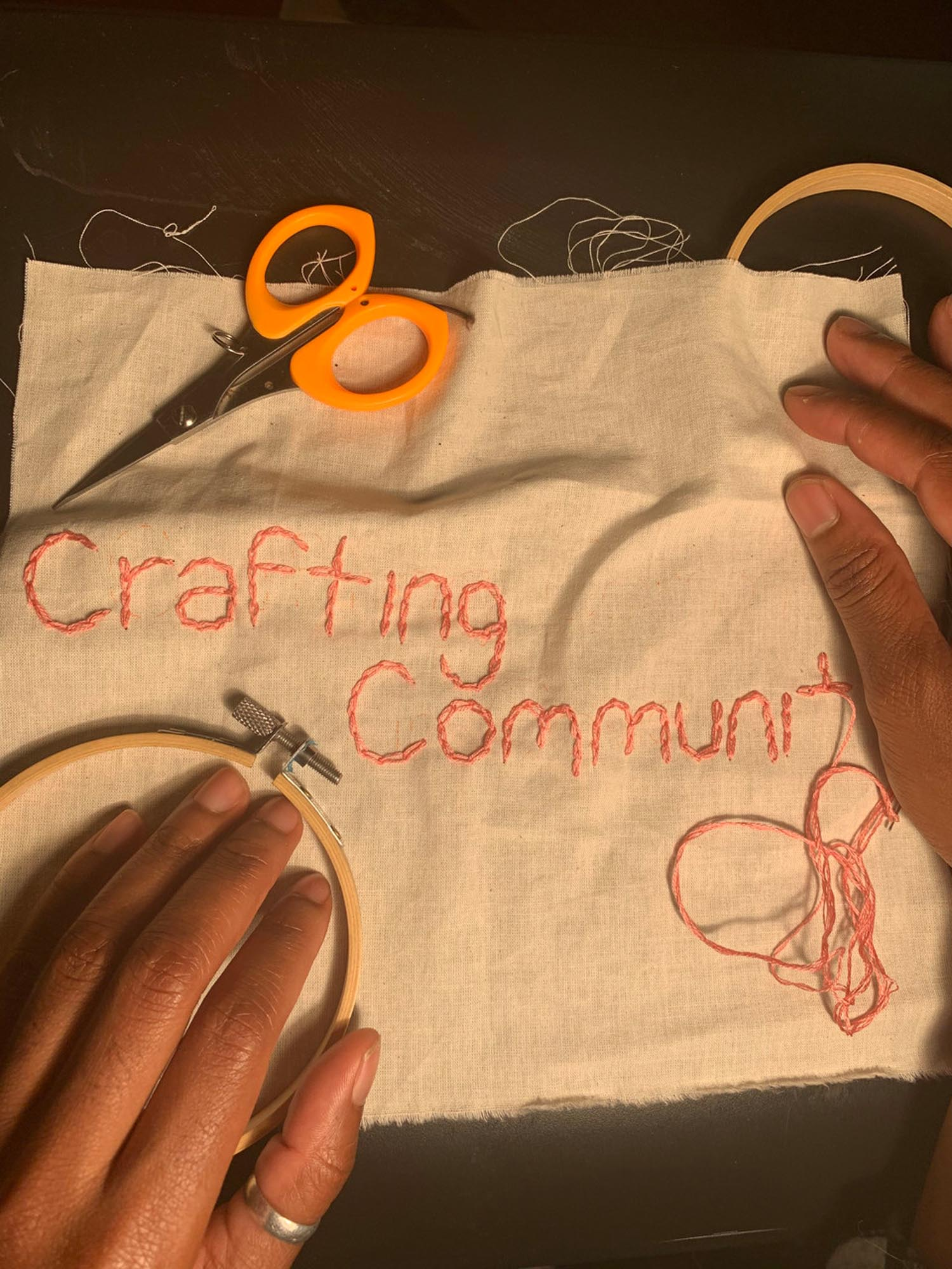 Brown hand rest atop a muslin square after having chain stitches the words Crafting Community into the fabric with pink thread. Orange handled scissors lie on the table nearby.