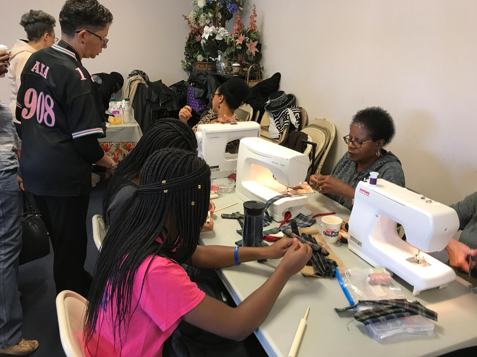 a group of women in a room closely sewing together on multiple white sewing machines