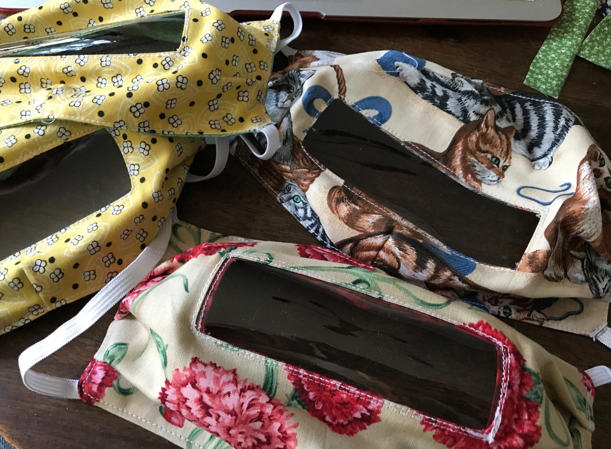 a pile of handmade face masks with windows, with bright floral fabrics