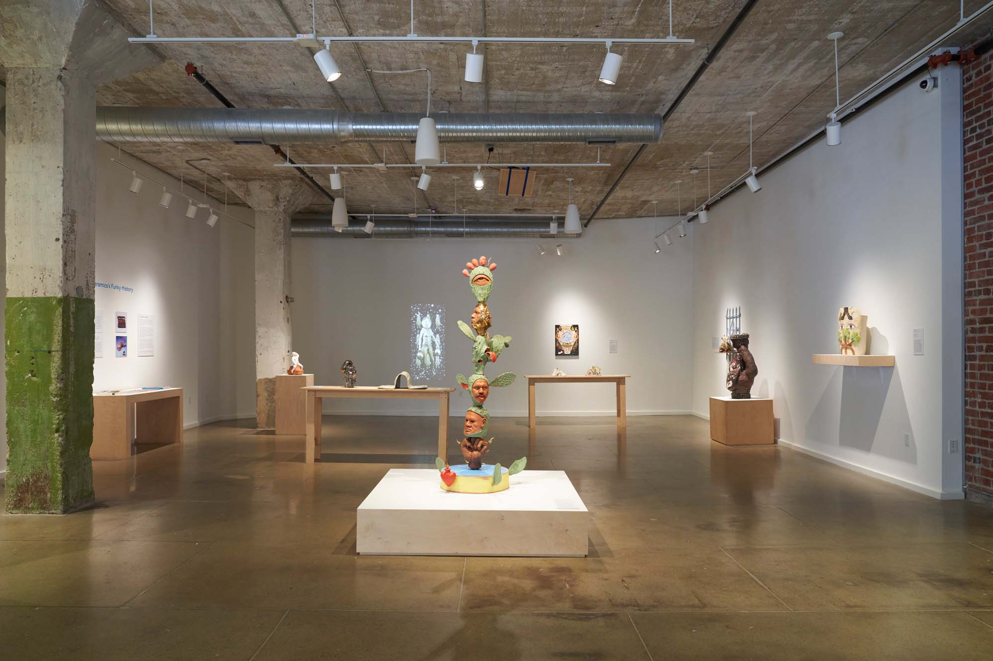 Image shows exhibition in gallery space with white walls. Ceramic sculptures are installed on pedestals, tables, and hanging from walls.