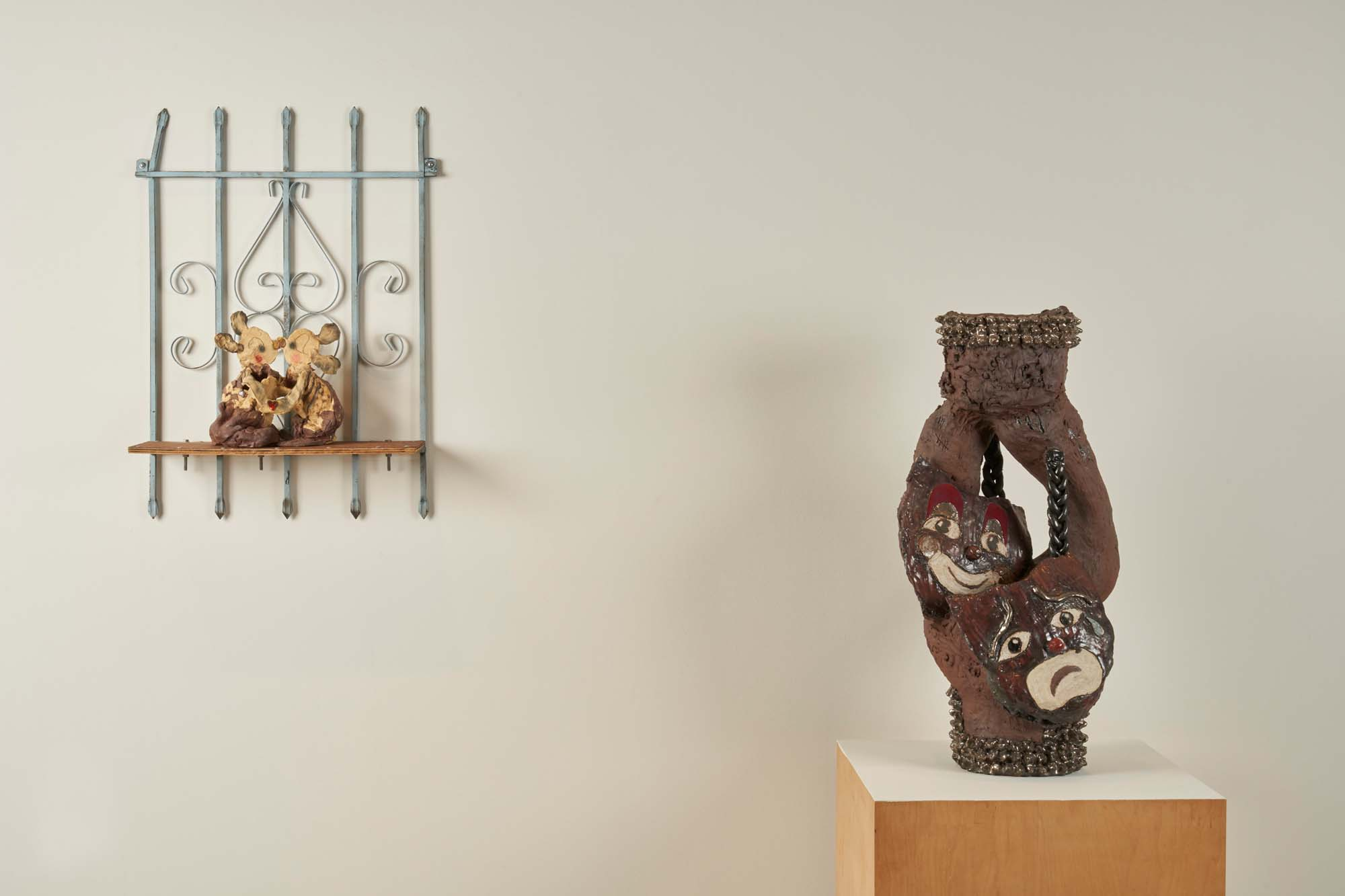 """Image of two ceramic sculptures by Diana Yesenia Alvarado, """"Kiss"""" (left) and """"Smile Now Cry Later"""" (right)."""