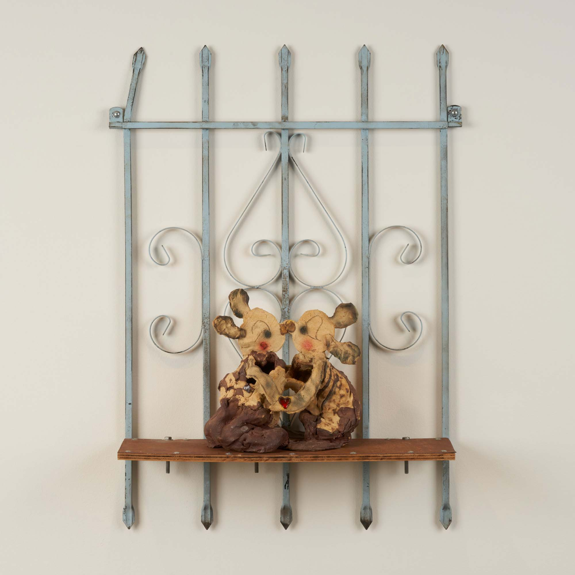 """Image of ceramic sculpture on shelf made from iron window grate, titled """"Kiss"""" by Diana Yesenia Alvarado."""
