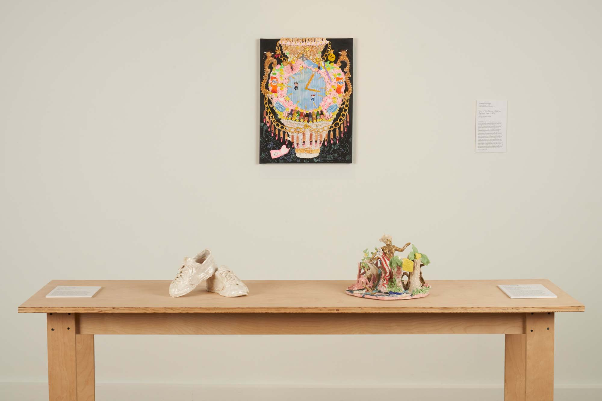"""Image of two ceramic sculptures, """"Killer Shoes"""" (left) and """"Alligator Boots"""" (right) and one acrylic painting, """"Vase of the Century 3"""", by Yvette Mayorga."""