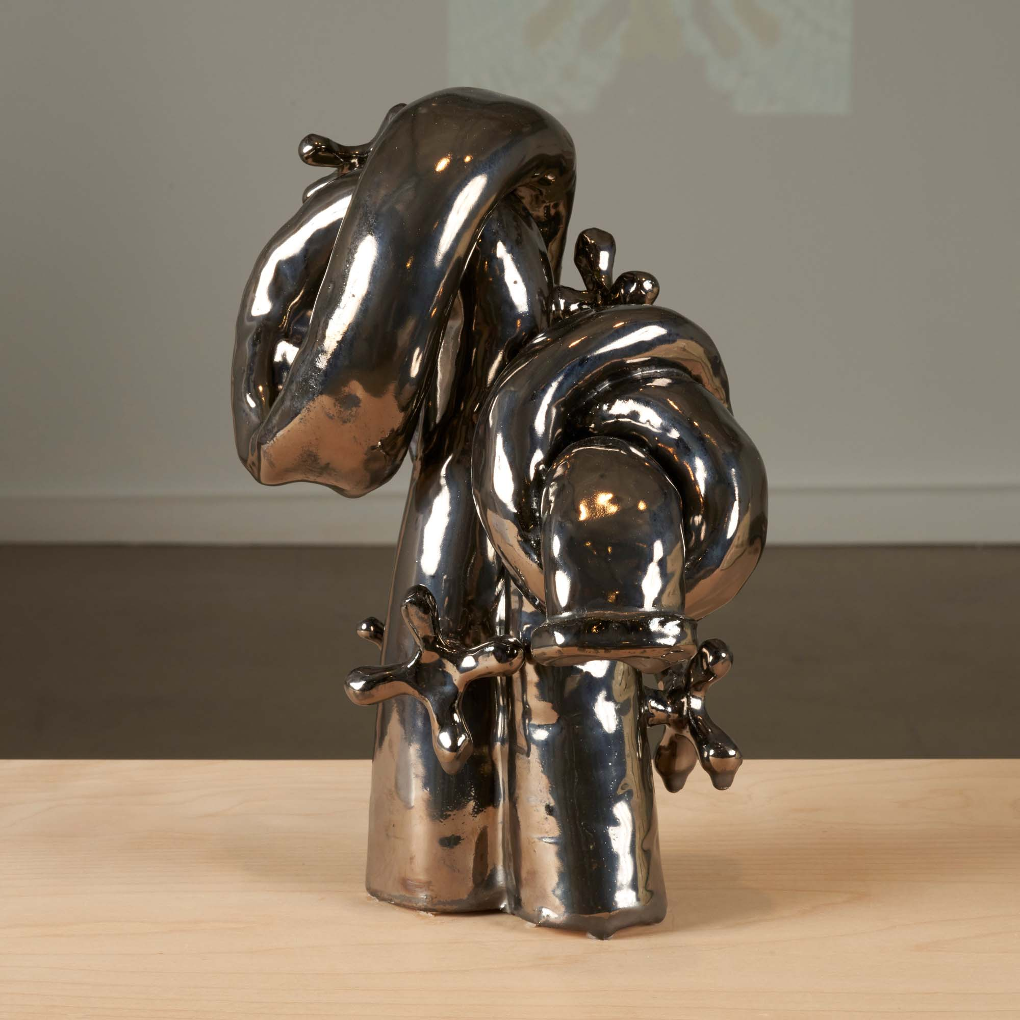 """Image of """"Outward and Bound"""" by Woody De Othello, a metallic-coated ceramic sculpture of a faucet."""